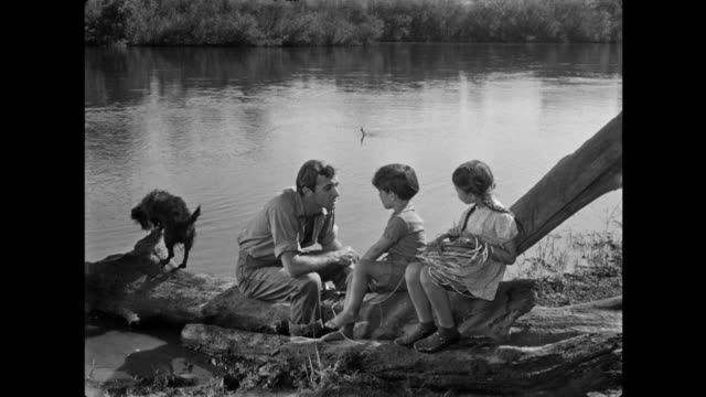 1940s man discusses catching fabled catfish with his children on the riverbank - fairytale stock videos & royalty-free footage