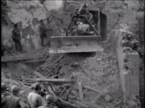 1940s man driving equipment to clear rubble, others watching / europe - rubble stock-videos und b-roll-filmmaterial