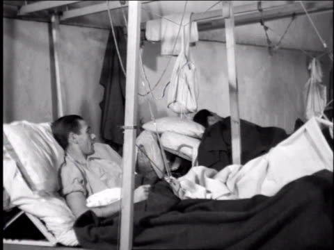 1940s ws man laying in military hospital bed with several injuries - orthopedic equipment stock videos & royalty-free footage