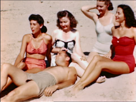 1940s man lying on beach surrounded by 4 women in swimsuits / 1 woman rubs his head - surrounding stock videos and b-roll footage