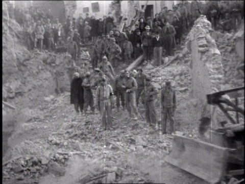 1940s man using bulldozer to clear rubble, many people on a hill watching / europe - rubble stock-videos und b-roll-filmmaterial