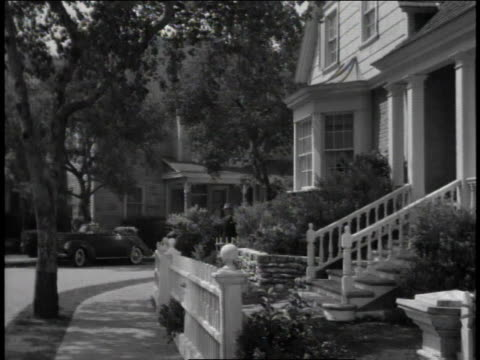 vidéos et rushes de 1940s zi man walking down quaint town's sidewalk and greeting a woman with a handshake / united states - l'amérique profonde