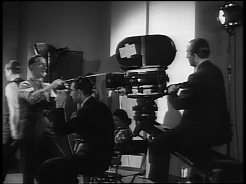 B/W 1940s man winding up tape measure to camera with cameraman sitting behind + director nearby