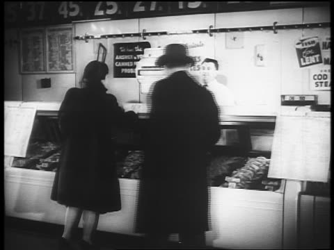 B/W 1940s man + woman walking by meat counter with smiling butcher / newsreel