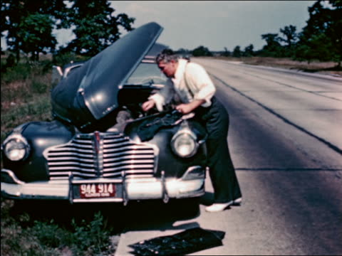 vidéos et rushes de 1940s man working on engine of car broken down beside highway / travelogue - panne de voiture
