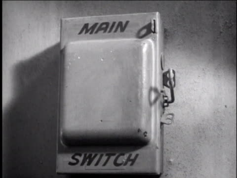 1940s CU man's hand switching off light at main switch box