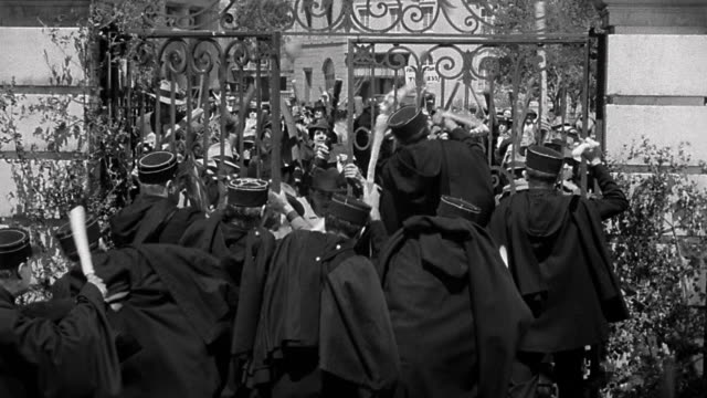 1940s medium shot angry mob with wooden clubs storming gate and attacking uniformed French policemen