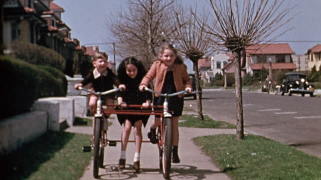 1940s medium shot boy and girl riding rigged double bicycle / other girl on roller skates hanging on