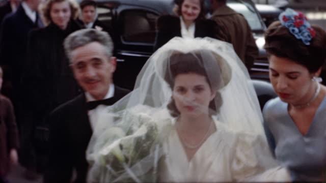 vídeos de stock e filmes b-roll de 1940s medium shot bride walking from car toward cam / accompanied by older man and woman - pai da noiva