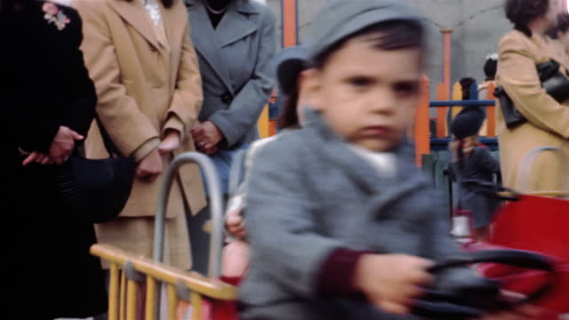 vídeos de stock, filmes e b-roll de 1940s medium shot children riding merry go round / boy on ride looking at cam with unhappy expression - meninos