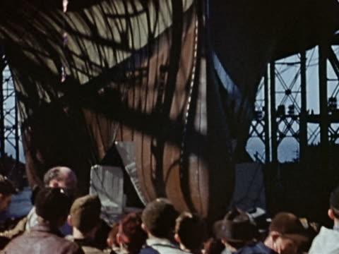 vídeos de stock e filmes b-roll de 1940s medium shot crowd watches as ship launches into waterway - construtor de navios