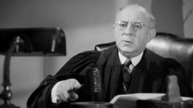 1940s medium shot male judge leaning forward and pounding gavel during trial - autorità video stock e b–roll
