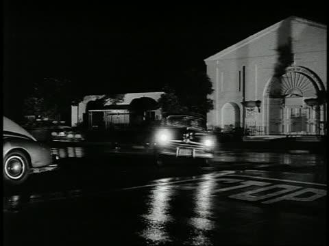 vidéos et rushes de 1940s medium shot pan 2 police cars chasing car around corner at night - poursuivre