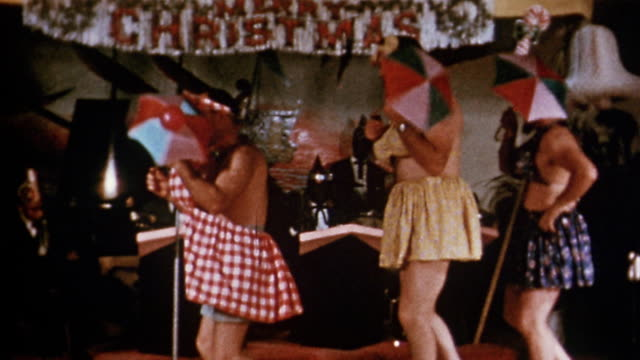 vídeos de stock, filmes e b-roll de 1940s medium shot pan four men in women's bathing suits walking across stage and twirling umbrellas - beauty queen