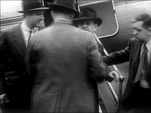 1940s Medium shot pan mobster being apprehended after getting off plane/ AUDIO