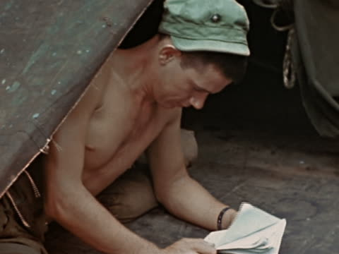 1940s medium shot shirtless sailor lying under tarp and reading letter in privacy - auf der seite liegen stock-videos und b-roll-filmmaterial