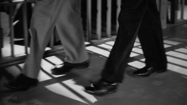 1940s medium shot tracking shot feet of guard and prisoner walking along cell block in jail, one man carrying key ring - jail cell stock videos & royalty-free footage