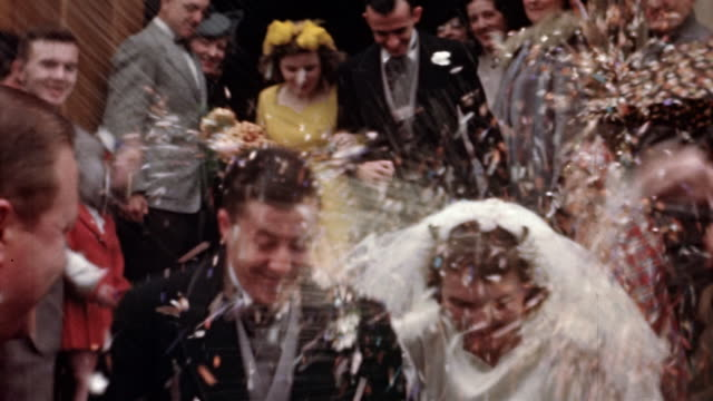 vídeos de stock e filmes b-roll de 1940s medium shot wedding guests throwing rice on bride and groom exiting chapel with wedding party - casamento