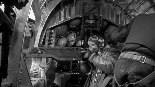 1940s medium shot wwii gunner firing gun in an airplane / man in foreground with back to camera - 20 29 years stock videos & royalty-free footage