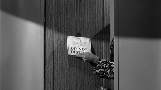 "vídeos de stock e filmes b-roll de 1940s medium shot zoom in hand hanging ""do not disturb"" sign on door - sob proteção"