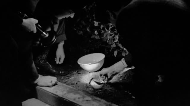 1940s medium shot zoom in to close up group of detectives with flashlight taking plaster impression of footprint - three people stock videos & royalty-free footage