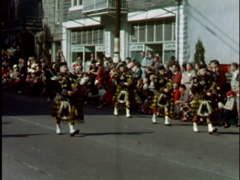 1940s WS, PAN, Men in kilts playing bagpipes marching in parade, Elkins, West Virginia, USA