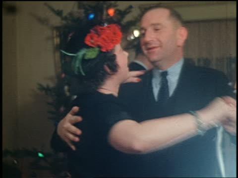 1940s middle-aged couple smiling + dancing in living room / christmas tree in background / home movie - christmas tree stock videos & royalty-free footage