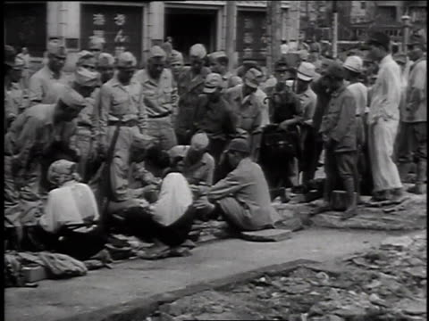 vídeos de stock, filmes e b-roll de 1940s montage a group of soldiers speaking with civilians some of them seated crosslegged on the ground / japan - guerra do pacífico