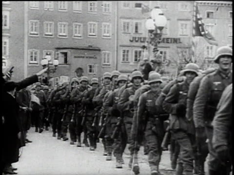 1940s montage austrians cheering and saluting german troops marching on the street / austria - ナチズム点の映像素材/bロール