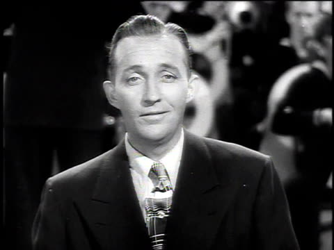 stockvideo's en b-roll-footage met 1940s montage bing crosby performing don't fence me in in front of a coast guard band / united states - zingen