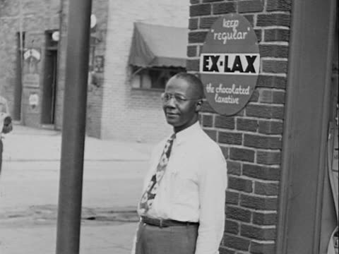 1940s MONTAGE B/W MS Man standing on street at store-front under 'Ex-Lax' sign/ MS Sign for 'Peoples Drug Co.'/ Greenwood, Tulsa, Oklahoma, USA