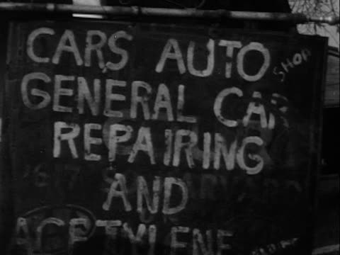 1940s montage b/w cu sign outside auto repair shop/ ms mechanic working on car in garage/ ms mechanic in overalls and welding mask/ ms man welding/ greenwood, tulsa, oklahoma, usa - metal industry stock videos and b-roll footage