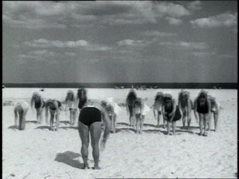 1940s MONTAGE Charles Atlas leads group of women exercising on a beach in swimsuits