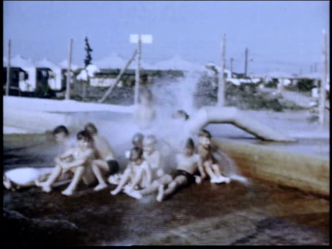 vídeos y material grabado en eventos de stock de 1940s montage children playing at gushing water pipe in alien detention facility / crystal city texas united states - bañador de hombre