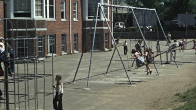 vídeos de stock, filmes e b-roll de 1940s ms ha montage children playing on seesaw and swings on school playground, columbia, missouri, usa - pátio de escola
