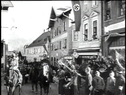 1940s MONTAGE crowds of Austrian people cheering and waving Nazi flags as German troops march by / Austria