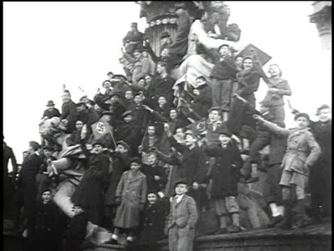 stockvideo's en b-roll-footage met 1940s montage crowds of austrian people cheering as german troops move in / austria - nazi vlag