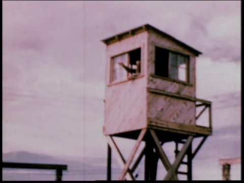 1940s MONTAGE Guard tower and barbed wire fence along the perimeter of camp / Crystal City Texas United States