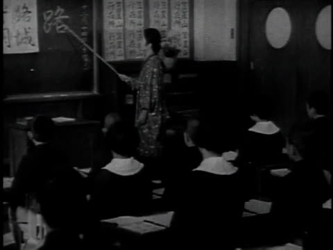 1940s montage japanese children in uniforms marching, learning to write, and listening to teacher / japan - japanese school uniform stock videos & royalty-free footage