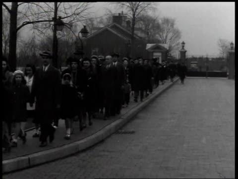 vídeos y material grabado en eventos de stock de 1940s montage lines of people in black walking down sidewalk / united states - luto