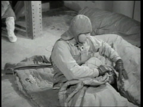 1940s montage men dressed in cold suits sitting in cold room while more men enter the room and begin laying down in sleeping bags while being monitored / fort knox, kentucky, united states - 寝袋点の映像素材/bロール