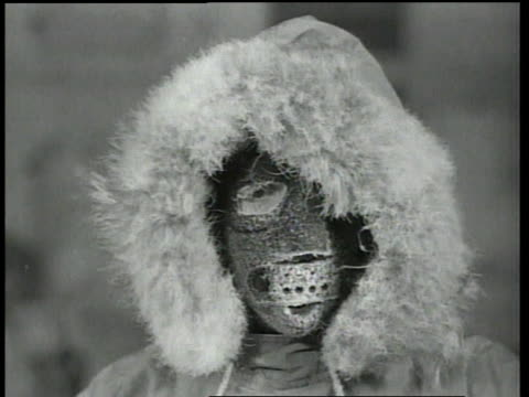 stockvideo's en b-roll-footage met 1940s montage men dressed in cold suits with big hoods and face masks jumping and moving to keep warm while you can see their breath in the air while in a cold room / fort knox, kentucky, united states - zichtbare adem
