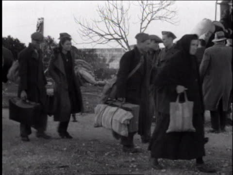 1940s montage refugees carrying belongings and loading onto truck / europe - rifugiato video stock e b–roll