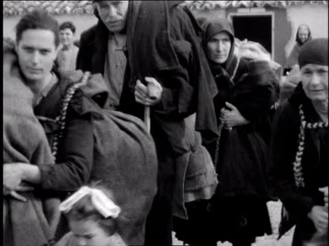 stockvideo's en b-roll-footage met 1940s montage refugees carrying large bundles on their backs / european theater of operations - vluchteling ontheemden