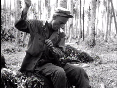 1940s montage soldier sitting cleaning rifle / europe - gewehr stock-videos und b-roll-filmmaterial