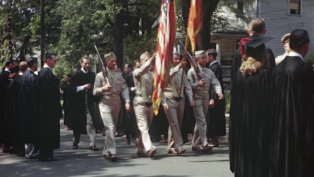 1940s MONTAGE MS Soldiers carrying pennant walking between graduates during parade, Columbia, Missouri, USA