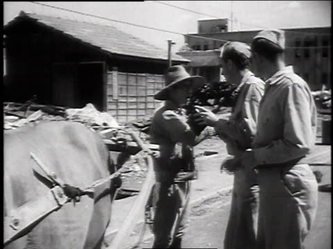 1940s montage soldiers speaking with a civilian, standing beside a yoked ox / japan - 働く動物点の映像素材/bロール