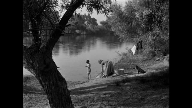 1940s mother hand washes clothes as son plays in the river - lava video stock e b–roll