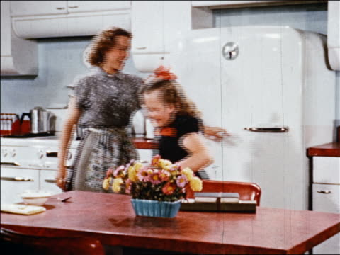 1940s mother takes can of fruit cocktail from refrigerator and serves it to girl at table after school