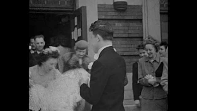 vídeos de stock, filmes e b-roll de 1940s newlywed couple pose for pictures outside of church while family and friends throw rice - 1940
